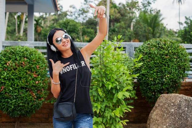 Mulher jovem e elegante hippie em camiseta preta, jeans, ouvindo música em fones de ouvido, se divertindo, posando, tirando foto de selfie no telefone, mostrando o símbolo da paz, expressão de carinha engraçada