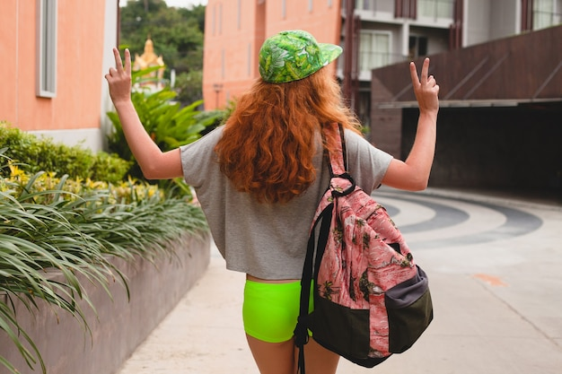 Mulher jovem e elegante hippie ruiva, caminhando na rua, boné verde, roupas da moda, roupa da moda, estilo adolescente urbano, mochila, viajante, vista de trás, mostrando o símbolo da paz,