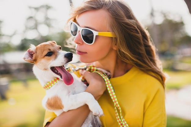 Mulher jovem e elegante hippie segurando um cachorro andando e brincando