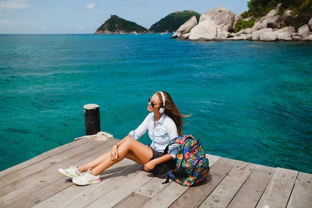 Mulher jovem e elegante hippie viajando ao redor do mundo, sentada no cais, óculos de aviador, fones de ouvido, ouvindo música, férias, mochila, camisa jeans, feliz, lagoa de ilha tropical