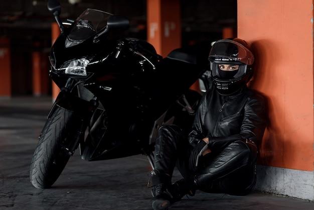 Mulher jovem e elegante motociclista com belos olhos, roupa de proteção preta e rosto cheio