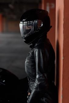 Mulher jovem e elegante motociclista com equipamento de proteção preto e capacete fechado perto da bicicleta