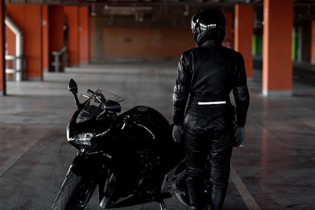 Mulher jovem e elegante motociclista com equipamento de proteção preto e capacete fullface perto de sua bicicleta