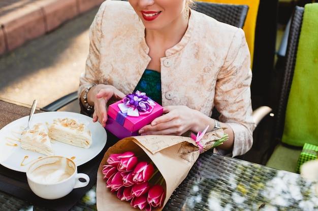 Mulher jovem e elegante sentada em um café, segurando uma caixa de presente, sorrindo