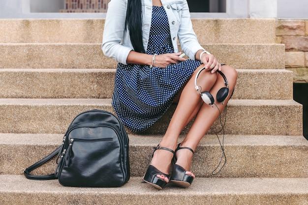 Mulher jovem e elegante sentada na escada, com fones de ouvido nas mãos, mochila, pernas longas, sapatos de salto alto, pele bronzeada, detalhes em close-up, acessórios