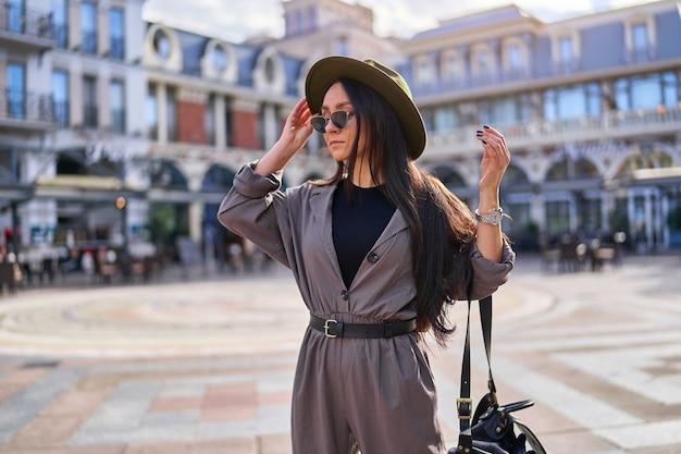 Mulher jovem e elegante viajante com chapéu de feltro, óculos escuros e macacão com mochila