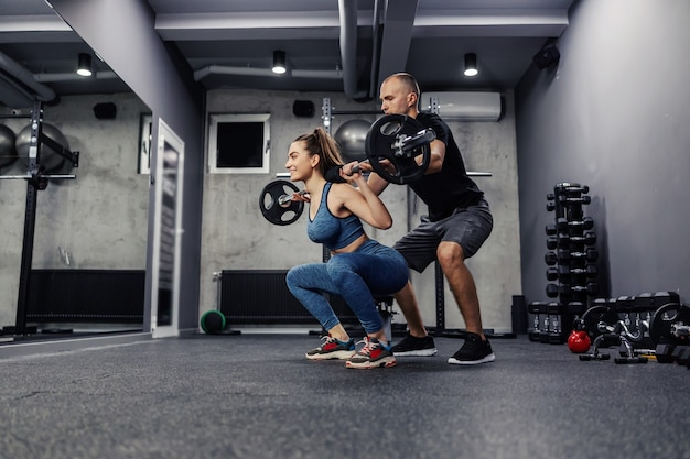 Mulher jovem e em roupas esportivas e em boa forma, faz agachamento com barra para fortalecer a musculatura de todo o corpo com treinador ajudando-a