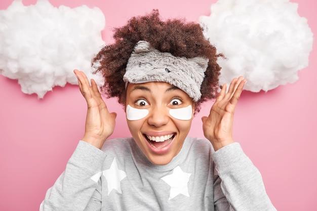 Mulher jovem e emocionada de alegria com cabelo encaracolado levanta as mãos e sorri amplamente reage a notícias incríveis pela manhã usa macacão com venda para reduzir rugas sob os olhos