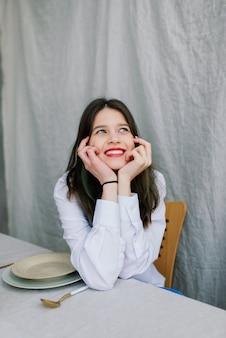 Mulher jovem e emocional alegre sentada à mesa de madeira com pratos na cozinha em casa