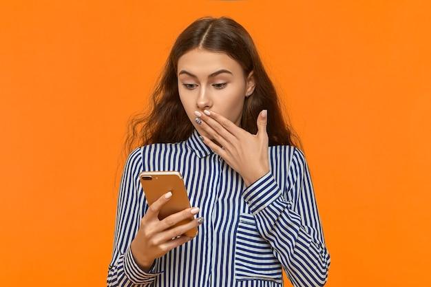 Mulher jovem e emocional com uma camisa listrada cobrindo a boca com uma expressão facial de choque e surpresa