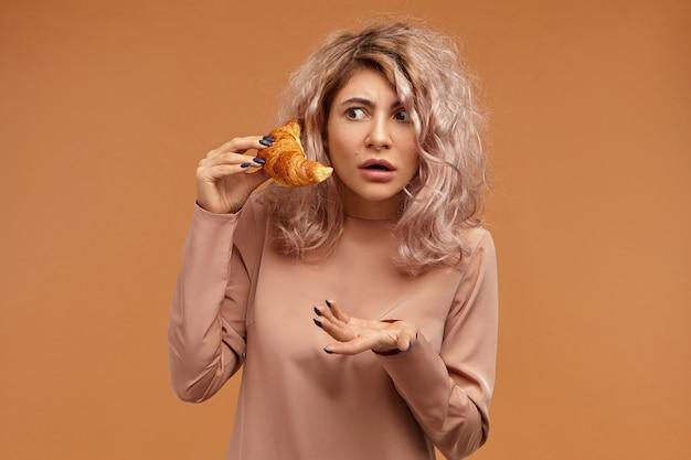 Mulher jovem e emocionalmente atraente com penteado bagunçado, confundindo a expressão facial perplexa, abrindo a boca