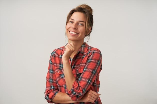 Mulher jovem e encantadora de cabelos castanhos com maquiagem natural, apoiando o queixo na mão levantada enquanto olha alegremente para a câmera com um largo sorriso, posando sobre fundo branco
