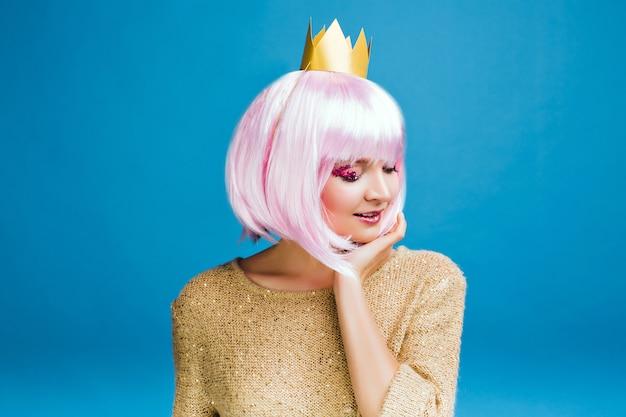 Mulher jovem e encantadora elegante com cabelo cortado rosa. suéter dourado, coroa na cabeça, sorriso de olhos fechados, verdadeiras emoções, hora de festa, maquiagem com enfeites rosa.