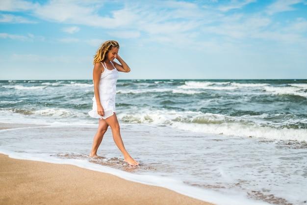 Mulher jovem e encantadora em um vestido branco caminha ao longo das ondas do mar calmo na costa arenosa do céu azul. nuvens brancas em um dia quente e ensolarado de verão