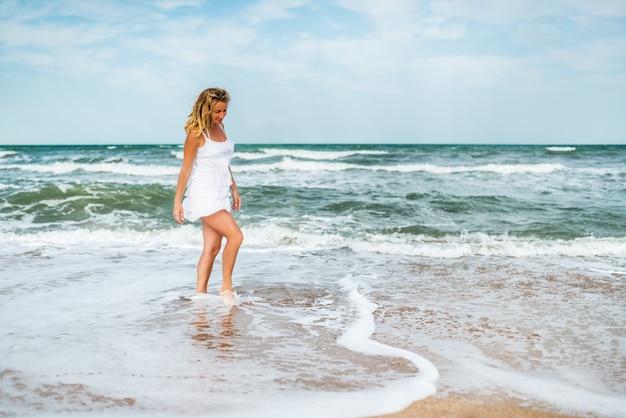 Mulher jovem e encantadora em um vestido branco caminha ao longo das ondas do mar calmo na costa arenosa no fundo do céu azul.