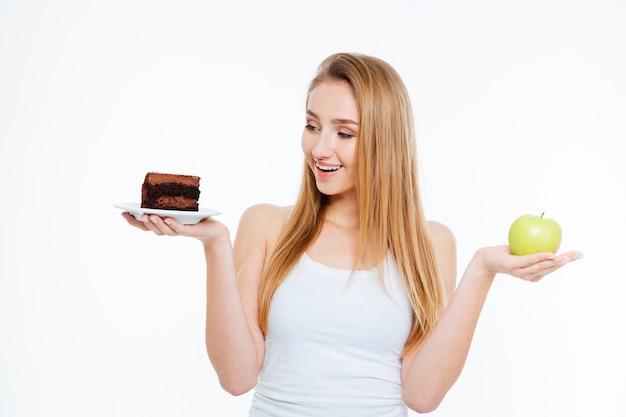 Mulher jovem e encantadora feliz em pé segurando bolo de chocolate e maçã verde sobre fundo branco