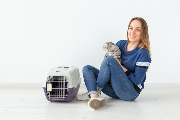 Mulher jovem e encantadora segura nas mãos seu lindo gato escocês cinza sentado no chão de um apartamento novo