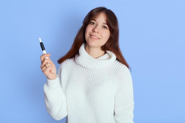 Mulher jovem e encantadora sobre azul, senhora de bom humor olha para a câmera e segura e ciggy na mão, vestindo um traje casual, tem cabelo escuro.