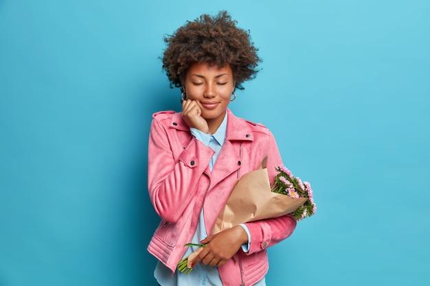 Mulher jovem e encaracolada satisfeita fecha os olhos e sente prazer segura flores embrulhadas em poses de papel com expressão alegre e usa uma jaqueta rosa isolada sobre a parede azul
