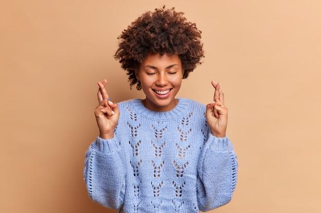 Mulher jovem e esperançosa com os dedos cruzados acredita que os sonhos se tornam realidade sorri amplamente mantém os olhos fechados usa um suéter de tricô isolado sobre a parede marrom do estúdio