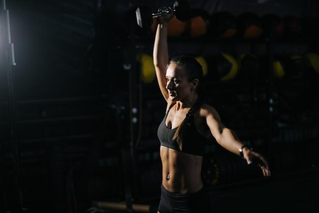 Mulher jovem e esportiva com corpo atlético perfeito, vestindo uma roupa esportiva preta levantando o kettlebell acima da cabeça