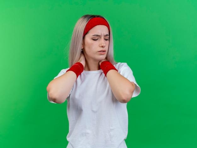 Mulher jovem e esportiva dolorida com aparelho e pulseira segurando o pescoço com as duas mãos, isolado na parede verde