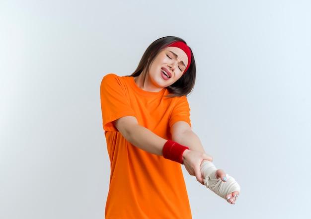 Mulher jovem e esportiva dolorida usando bandana e pulseiras segurando o pulso ferido envolto em bandagem com os olhos fechados isolados