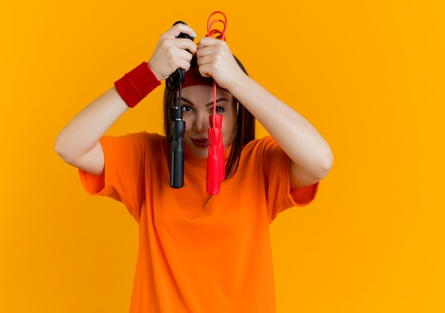 Mulher jovem e esportiva satisfeita usando bandana e pulseiras segurando cordas de pular, mantendo-as perto do rosto, isoladas na parede laranja com espaço de cópia
