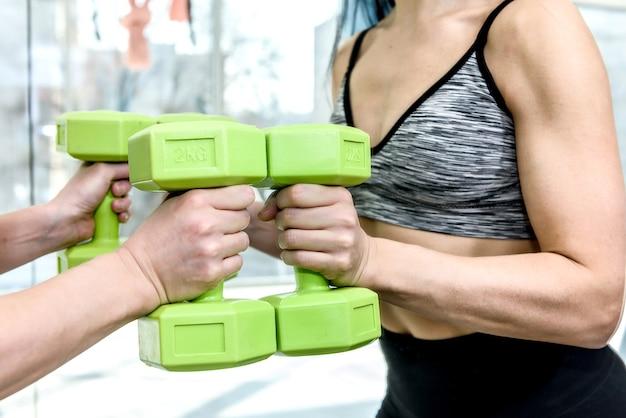 Mulher jovem e esportiva se exercitando na academia com halteres