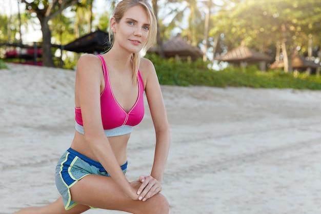 Mulher jovem e esportiva vestida com roupas esportivas brilhantes, faz exercícios durante o treinamento matinal na praia, trabalha os músculos das pernas, pratica esportes ao ar livre, faz exercícios de alongamento, tem corpo esguio