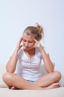 Mulher jovem e estressada com uma forte e terrível dor de cabeça, sofrendo de enxaqueca crônica
