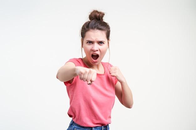 Mulher jovem e expressiva de cabelos castanhos com maquiagem natural, boxe com punhos erguidos e gritando com raiva enquanto está de pé sobre um fundo branco em roupa casual