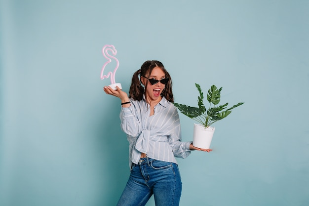 Mulher jovem e expressiva engraçada com cabelo escuro, vestindo camisa azul e jeans, posando com um sorriso maravilhoso segurando um flamingo rosa e um vaso de flores contra a parede azul