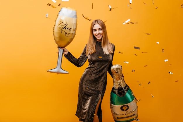 Mulher jovem e fascinante com expressão de rosto feliz à espera da festa de aniversário. retrato interior de mulher de cabelos louros bem torneada com garrafa de champanhe e um copo de vinho.