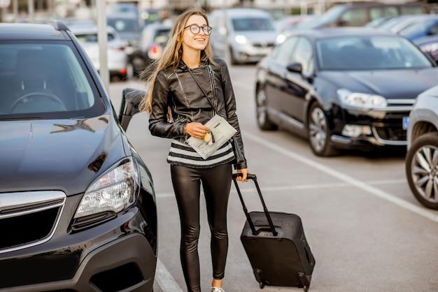 Mulher jovem e feliz andando com uma mala segurando um contrato de locação no estacionamento