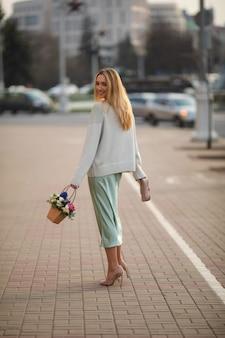 Mulher jovem e feliz, branca, com cabelo longo loiro, caminhando para a rua com um boquet de lindas flores no verão