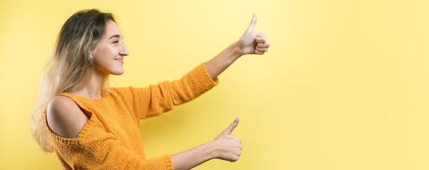 Mulher jovem e feliz, branca, com um suéter laranja, fazendo sinal de polegar para cima e sorrindo. bom trabalho