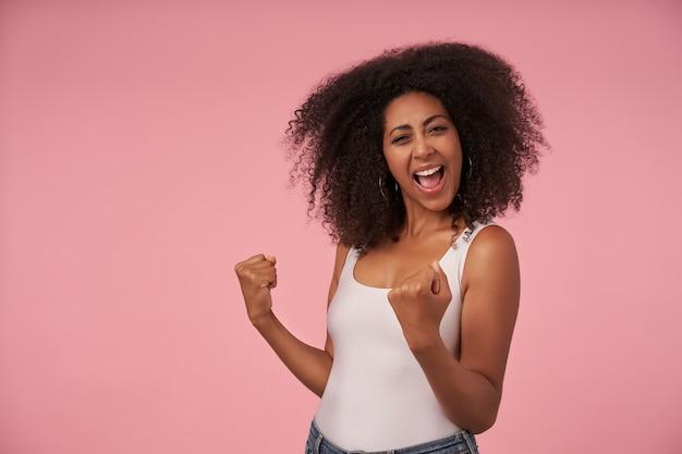 Mulher jovem e feliz cacheada com penteado casual e sorriso largo e alegre, comemorando a vitória de seu time favorito, isolada na rosa com os punhos levantados