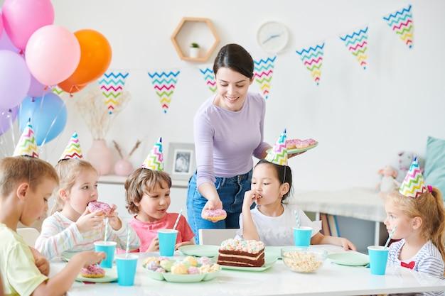 Mulher jovem e feliz casual colocando um donut na mesa servida enquanto o serve para uma festa de aniversário para crianças pequenas