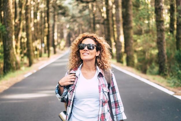 Mulher jovem e feliz, caucasiana, caminhando e viajando em uma estrada com uma floresta