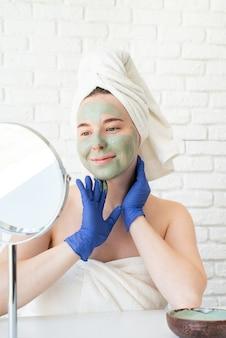 Mulher jovem e feliz caucasiana em toalhas de banho brancas usando luvas, aplicando máscara facial de argila, olhando para o espelho