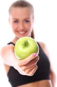 Mulher jovem e feliz com maçã verde