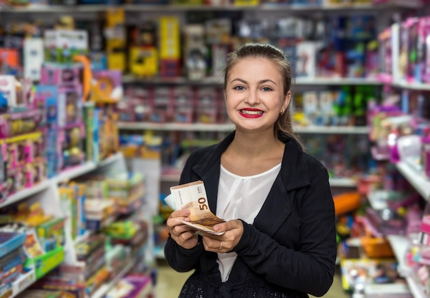 Mulher jovem e feliz com notas de euro, posando na loja de brinquedos