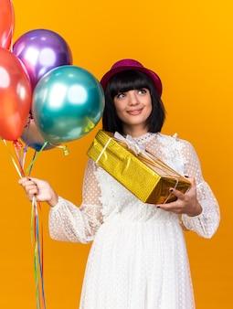 Mulher jovem e feliz com um chapéu de festa segurando balões e um pacote de presente olhando para cima, isolado na parede laranja