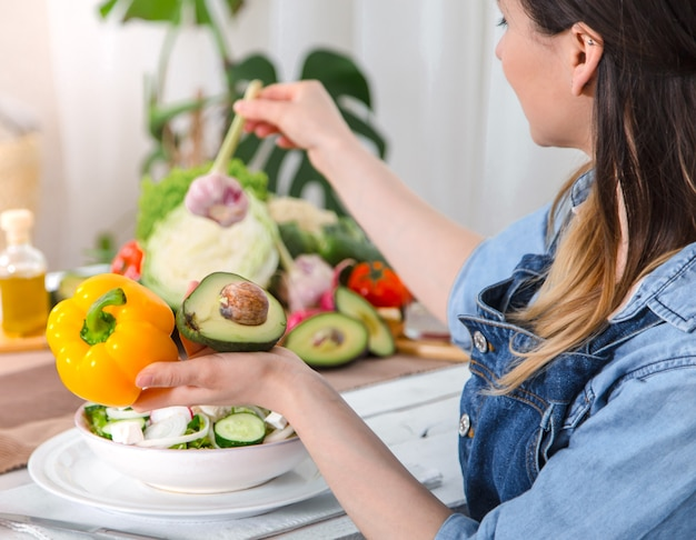 Mulher jovem e feliz comendo salada na mesa