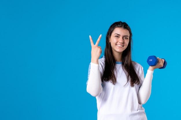 Mulher jovem e feliz de frente segurando halteres azuis