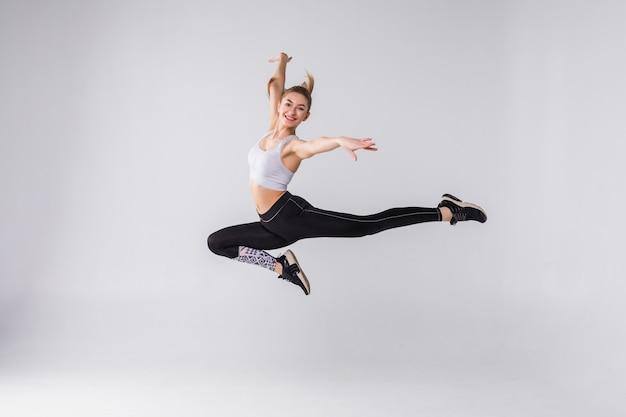Mulher jovem e feliz e alegre em fitness pulando