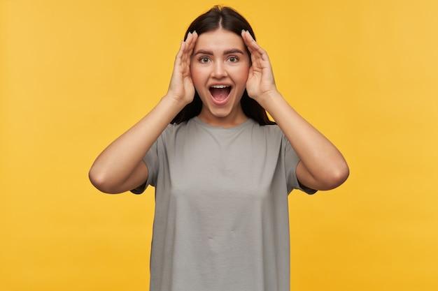 Mulher jovem e feliz e brincalhona com cabelo escuro e boca aberta em uma camiseta cinza parece animada e jogando esconde-esconde sobre a parede amarela