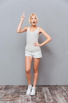 Mulher jovem e feliz e inspirada apontando para cima e tendo uma ideia sobre a parede cinza