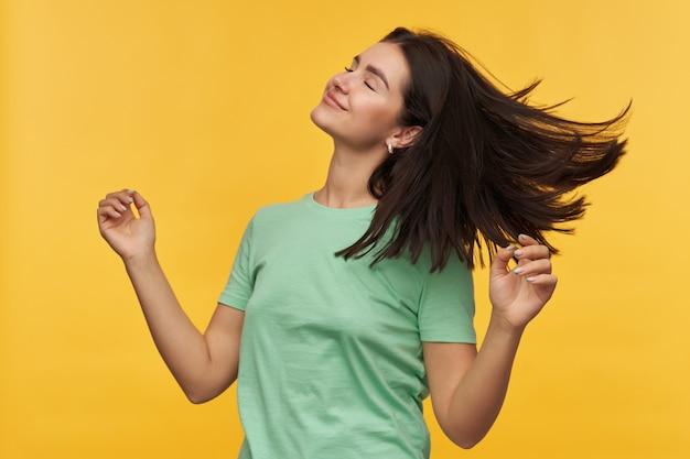 Mulher jovem e feliz e relaxada com cabelo escuro e camiseta menta fica com os olhos fechados e dançando sobre a parede amarela